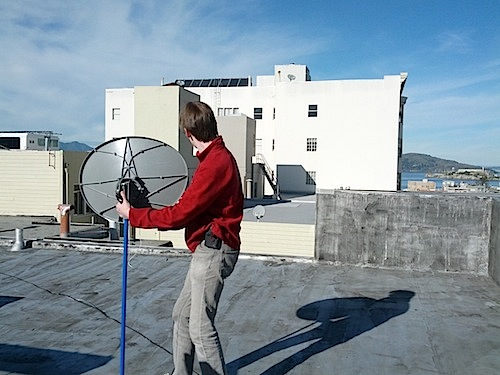 [Aiming the dish at a building]